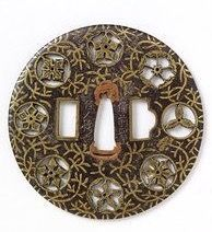 Hand-guard (tsuba) for a sword, iron with brass plugs pierced to depict various heraldic badges and inlaid brass depicting waterweed. Signed made by Hakamaya Saburodayu of Okayama in Bizen province, yoshiro-zogan type, ca.1600-1650.