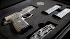The new SIG Legion P-229 in it's hard case with three mags, challenge coin and folder knife.
