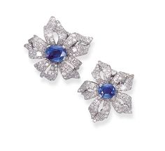 A PAIR OF SAPPHIRE AND DIAMOND CLIP BROOCHES, BY CARTIER   Each designed as circular-cut diamond flowers, with curling petals, to the central oval-cut sapphire, weighing 2.84 and 5.30 carats, with French assay marks for platinum  Signed Cartier, Paris
