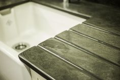 Close up image of a modern natural stone slate sink surround with an inset Belfast sink.