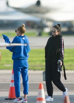 Low-key: The duo were clearly on the same page style-wise as they donned Champion tracksuits and matching hairstyles as they touched down on the tarmac
