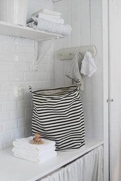 black and white striped laundry bag in white laundry room