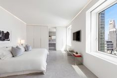 This all white master bedroom, complete with an ensuite bathroom, maximizes storage space and minimizes clutter.