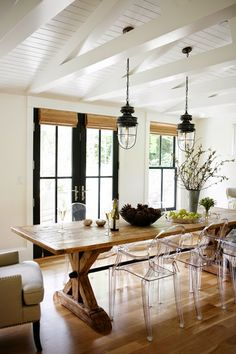 Modern Farmhouse kitchen dining area, lucite side chairs, Wingback chairs at head of table and industrial lighting, beams, roman shades on french doors of steel.
