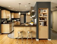 Maple Kitchen with light wood floor and dark counters and vertical accents.