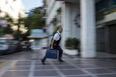 Athens, Greece  -   A security worker brings money to a National Bank branch. The country faces a default that could push it out of the euro and cause ripple effects across the European economy -  Photograph: Marko Djurica/Reuters