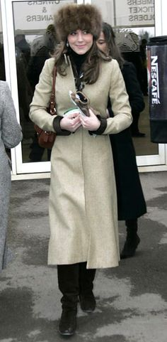 classic wool top coat and fur hat with brown over-the-shoulder handbag and tall boots