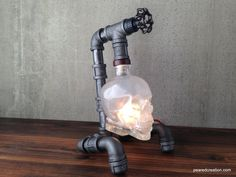 This lamp is constructed from industrial style black iron piping and the unique Crystal Head Vodka bottle. The skull bottle is firmly secured
