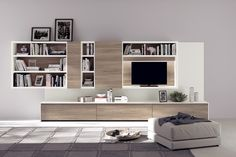 "This #living-room composition features bookcases, open units, doors on the ""Fluida"" wall system as well as a space for a TV; the base units are characterized by doors and back panels in Navajo Elm decorative melamine. The ""Fluida"" wall system structure is in Pure White Melamine, the top, back panels and side-facing panels are in White laminate."