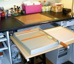 Use heavy duty shelf/drawer guides to add a large pull out shelf right below work space for paper cutter and scoring board.