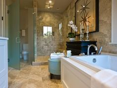 Travertine-style porcelain tile clads floors and wall surfaces in the master bathroom, lending a sandy beach style to the interior.