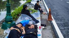 Am Donnerstag wird Thailands verstorbener König Bhumibol eingeäschert. Schon Tage vorher campieren Hunderte Menschen an der Strecke, um sich einen guten Platz für die feierliche Prozession zu sichern. Es wird erwartet, dass eine Million Menschen die 1,9 Kilometer lange Strecke zu dem Feld säumen werden, wo die sterblichen Überreste Bhumibols eingeäschert werden. | Bildquelle: dpa