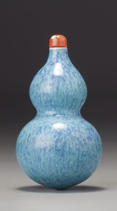 A 'ROBIN'S EGG' PORCELAIN 'DOUBLE-GOURD' SNUFF BOTTLE PROBABLY IMPERIAL, QING DYNASTY, QIANLONG / EARLY JIAQING PERIOD, of double-gourd form with a convex lip, applied with a mottled turquoise and lavender-blue glaze, the base with spur marks; with a coral stopper
