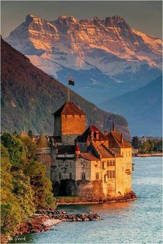 "Sunset over Château de Chillon -an island castle located on Lake Geneva, south of Veytaux in the canton of Vaud, Switzerland. It is situated at the eastern end of the lake, on the narrow shore between Montreux and Villeneuve, which gives access to the Alpine valley of the Rhone. Chillon is amongst the most visited castles in Switzerland and Europe. It is also known to be the inspiration behind the castle in ""The Little Mermaid"" movie."
