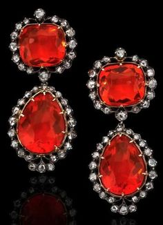 A pair of early 19th century fire opal and diamond earrings Each formed as a cushion-cut fire opal suspending an articulated drop set with a pear-cut fire opal, all surrounded by rose-cut diamonds, mounted in silver on gold, length 42mm, later screw back fittings, the fire opals estimated to weigh approximately 3.87cts, 3.58cts, 4.84cts and 3.96cts, to a case retailed by A. Marx, London