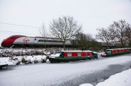 Frozen canal with boats and a Virgin Pendolino