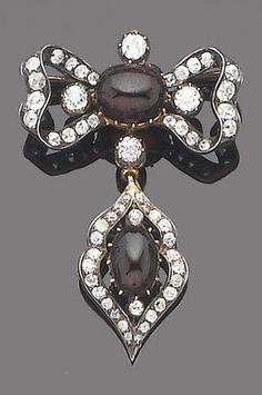 A garnet and diamond bow brooch, circa 1880. The openwork ribbon bow set to the centre with a cabochon garnet, within an old brilliant-cut diamond surround, suspending a detachable similarly set drop of openwork design, mounted in silver and gold, detachable brooch fitting.