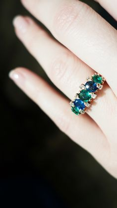 Antique Victorian rose gold five stone ring featuring two natural sapphires weighing approximately one carat total, and three natural emeralds weighing approximately .65 carats total. Accented with eight single cut diamonds. Circa 1895.
