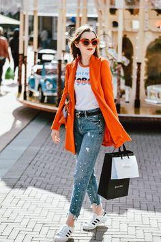 O acessório vintage que dá aquele up no look. Óculos gatinho, t-shirt estampada, blazer laranja, calça jeans destroyed, tênis adidas branco