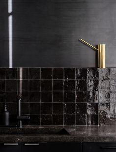 Black Moroccan tile kitchen backsplash and gold watering can