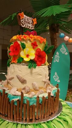 """Hawaiian themed baby shower cake! This was a 3 tier cake. The top 6"""" cake was vegan double chocolate four layer chocolate cake with chocolate chips and filled with a vegan rum and chocolate ganache. Frosted with a vegan salted vanilla buttercream. 8"""" Middle layer was a vanilla piña colada butter cake with a pineapple rum buttercream. 12"""" bottom was a 3 layer torted dark chocolate cake with a rum, coconut, and chocolate ganache. Decorated with chocolate seashells, gumpaste flowers, & wafers!"""