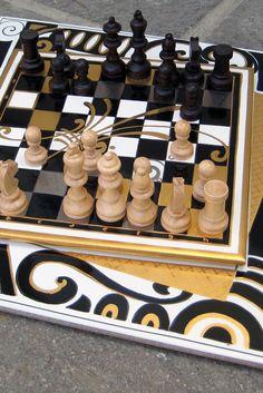 Schachspiel. Schwarz mit Echtgold. 2 Teilig. Die Schachfläche ist abnehmbar. Auf der größeren Fläche können auch Gläser und Karaffen aufbewahrt werden.