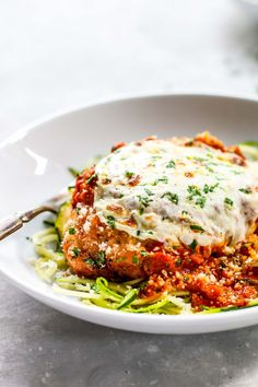 Healthy Chicken Parmesan that is crispy, cheesy, saucy, and served over zucchini noodles. So easy! 350 calories.
