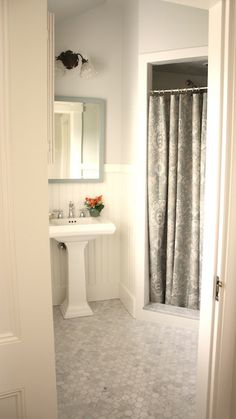 Stunning guest bathroom with gray walls paint color, glossy white pedestal sink, white chair rail & beadboard painted Benjamin Moore White Dove, gray mirror, paisley shower curtain and white carrara marble hex tiles floor.   Benjamin MooreMoonshine