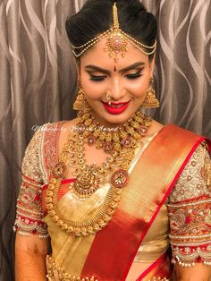Monisha looks ethereal and regal for her muhurtham. Hair and makeup by Vejetha for Swank. South Indian bride. Bridal makeup. Red lips. Bridal gold jewellery. Vintage gold jewellery. Jhumkis. Nose ring. Maang tikka. Bridal silk saree. Designer sari blouse. Winged eyeliner.