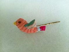 Embroidered bird on a hair slide.
