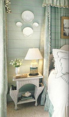 simple white seashell plates against a pale aqua wall & a white wicker night stand..lovely