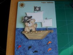 Step by step pirate bear in boat topper on Craftsuprint designed by Sharon Poore - made by Anne-marie wheeler - Cut out sheet and layered with foam pads used a blue card then added blue paper for the sea, punched some little fishes and added sun to finish it off. Fab design and very easy to make. - Now available for download!