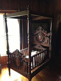 Fabulous antique four-postered baby bed believed to be walnut, late 19th century and possibly French. It is put together with just 4 pins and 2 knobs for the cradle which does rock.                                                                                                                                                      More
