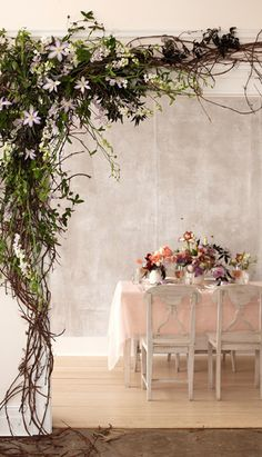 Natural branch and flower door arch decoration. Lots of vines growing from the floor upwards and along.