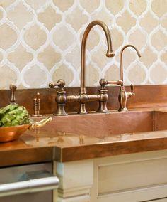 "A countertop and sink in copper inspired the kitchen's color scheme.    Sources:  Countertop (""Roja Alicante Marble""): Eastern Stone, 914/937-2100, easternstoneny.com. Backsplash (""Treble""/Bourbon Street Caramel, Jazz Glass Collection): Artistic Tile, 877/528-5401, artistictile.com.  Faucets (Vintage Collection): Whitehaus Collection, whitehauscollection.com. Available through Bilotta Kitchens of New York, 866/245-6882, bilotta.com."