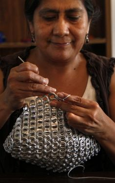 Guadalupe Acevedo creates a handbag from aluminum pop tops and thread at La Maestra Clinic in Vista.