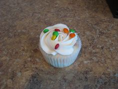 White cupcake with mini M&M's and butter creme frosting