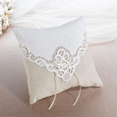 """A tan cotton pillow with ivory lace overlay and satin bow becomes a charming accent for the wedding ceremony. It measures 7.75""""."""
