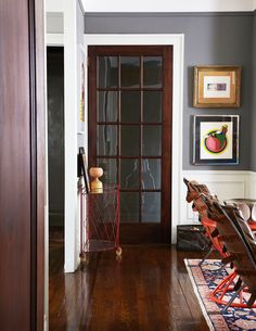 Glass and wood door in dining space with industrial leather dining chairs and small gallery wall