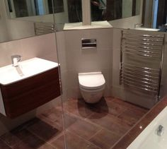 Corner Toilet/WC to make the most of space. Create the illusion of a bigger room by using large mirrors, wall hung WC and Basin unit. One of our past projects - Bathroom Boutique Ltd (Essex & London)
