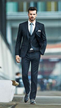 Comprar ropa de este look: https://lookastic.es/moda-hombre/looks/traje-de-tres-piezas-camisa-de-vestir-zapatos-derby-corbata-panuelo-de-bolsillo-correa/9399 — Camisa de Vestir Blanca — Corbata Celeste — Pañuelo de Bolsillo a Lunares Blanco — Traje de Tres Piezas Negro — Correa de Cuero Marrón Oscuro — Zapatos Derby de Cuero Negros