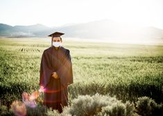 #Senior Boy poses cap and gown #Outdoors in #Field sun flare #pandemic