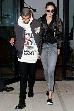 Gigi Hadid and Zayn Malik, wearing a Burberry studded leather jacket, grey jeans and black leather slip-on sneakers.