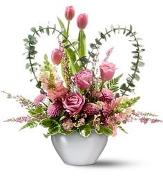 Tender Hearts  Pink tulips and snapdragons, lavender roses and button spray chrysanthemums and heather – accented with spiral eucalyptus, variegated pittosporum and leatherleaf fern – in a wisteria jardinière.