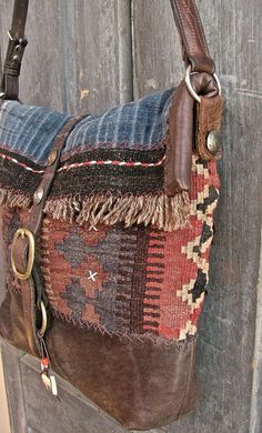 kinda lovin' this...The Buffalo bag messenger bag. Vintage kilim, Hmong indigo, bridle leather and old coins. Fully lined with African mud cloth....