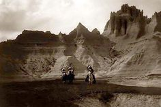 An historic image of the Indian Bad Lands. It was taken in 1905 by Edward S. Curtis.    The image shows Three Native Americans on horseback.