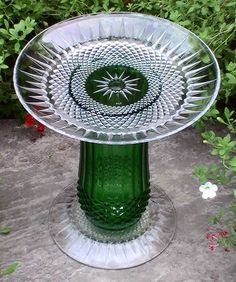 Glass Garden Ornament Bird Bath Pedestal Diamond Point Green Mystique  The name of this piece is Mystique. Accented with a green center section and crystal diamond point glass pattern in the both the bottom and the top plate. The center section is gently ridged with a diamond point pattern in the glass around the lower section. It stands approximately 11.5 inches high and 10 inches wide. Best use for this piece is as a bird feeder, bird bath, or as a pillar or plant stand.