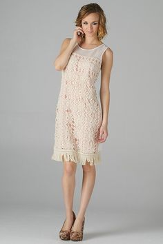 Ecstasy in this sophisticated sleeveless crochet layered cocktail dress has a fringe hem and mesh neckline.