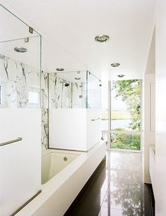 The sandblasted glass on the showers provides privacy while maintaining the simple sleek look from glass.