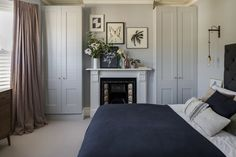 Interior Design by Imperfect Interiors at this Victorian terraced house in Balham, London. A palette of contemporary paint colours mixed with traditional period details- Paint & Paper Library Lead 5 on the walls, charcoal grey fabric headboard, washed linen curtains, white fireplace & Buster & Punch brass wall lights make the master bedroom feel grown up and luxurious. Photo by Chris Snook